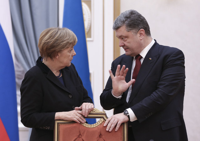 German Chancellor Angela Merkel and Ukrainian President Petro Poroshenko talk in Minsk, Belarus, Wednesday, February 11, 2015. (Photo by Mykhailo Palinchak/AP Photo)
