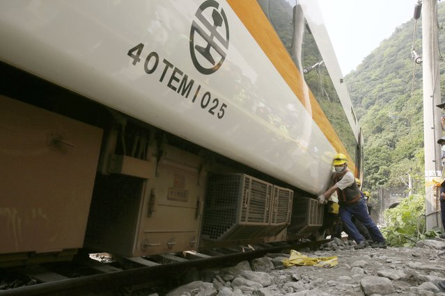 Workers try to remove a part of the derailed train near Taroko Gorge in Hualien, Taiwan on Saturday, April 3, 2021. The train partially derailed in eastern Taiwan on Friday after colliding with an unmanned vehicle that had rolled down a hill, killing and injuring dozens. Workers began removing some of the train cars and repair work also has begun on the tracks including the tunnel where part of the eight-car train crashed. (Photo by Chiang Ying-ying/AP Photo)