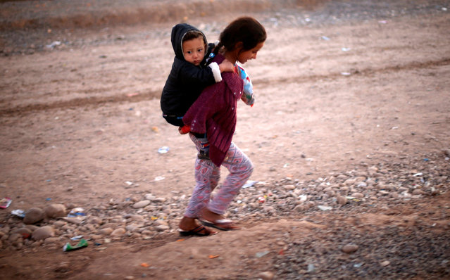 A displaced Iraqi girl, who fled the Islamic State stronghold of Mosul, carries her brother as she walks at Khazer camp, Iraq November 28, 2016. (Photo by Mohammed Salem/Reuters)