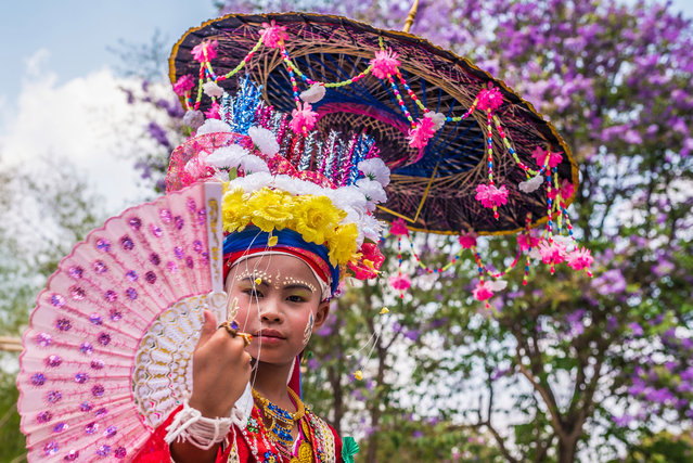 An initiate sprays out his fan as he enjoys the view from atop his father's shoulders during the ceremony in Mae Hong Son, Thailand, April 2016. (Photo by Claudio Sieber/Barcroft Images)