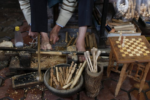 A man sculpts wood in traditional way by using toes in his workshop in the old Medina of Marrakesh December 13, 2014. (Photo by Youssef Boudlal/Reuters)