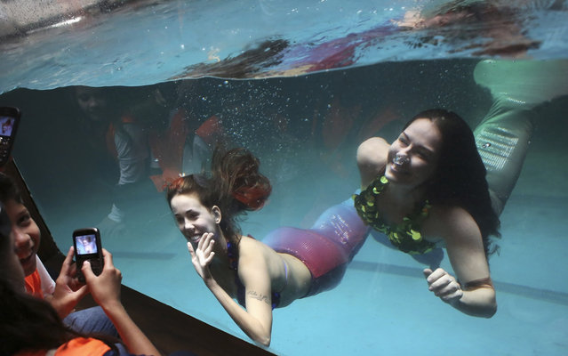 Women dressed as sirens perform from inside a tank as school children use their mobile phones to take photos of them at the Sao Paulo Aquarium September 17, 2013. According to organizers, the performance aims to narrate school children about Myth and Legend of the Sirens. (Photo by Nacho Doce/Reuters)