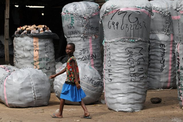 A girl walks past bags of shoes packed for transportation to Cameroon at Ariaria market in Aba, Nigeria August 19, 2016. (Photo by Afolabi Sotunde/Reuters)