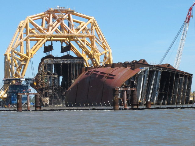 A towering crane pulls the engine room section away from the remains of the capsized cargo ship Golden Ray on Monday, April 26, 2021, offshore of St. Simons Island, Ga. The South Korean vessel capsized with roughly 4,200 vehicles in its cargo decks in September 2019. The engine room section is the fourth giant chunk of the ship to be cut away and removed since demolition began in November 2020. (Photo by Russ Bynum/AP Photo)