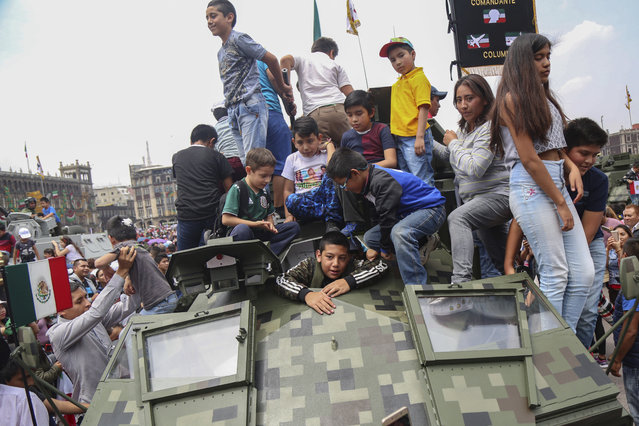 Children climb on a military vehicle displayed for Independence Day after a military parade, in the Zocalo of Mexico City, Sunday, September 16, 2018. Mexico is celebrated its independence from Spain. (Photo by Anthony Vazquez/AP Photo)