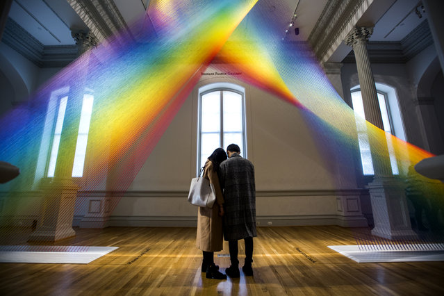 Visitors review their cell phone photos of an installation called 'Plexus A1' by artist Gabriel Dawe, one of nine large-scale art installations displayed at the 'Wonders' exhibit at the Renwick Art Gallery in Washington, DC, Wednesday, January 13, 2016. Built in the 1860s, the Renwick was the first American building to be designed specifically as an art museum; it recently reopened after a two year renovation. (Photo by Jim Lo Scalzo/EPA)