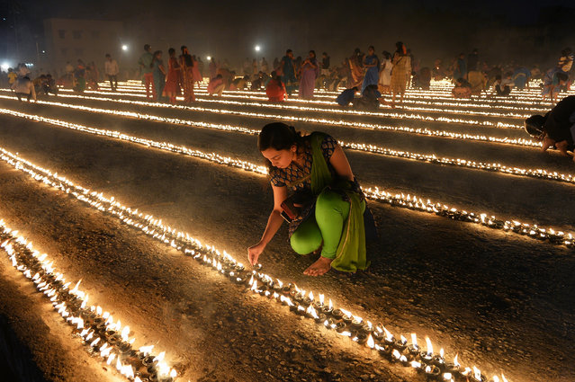 "Hindu devotees light oil lamps as part of ""Laksha Deepotsava"" (celebration of a hundred thousand lights), held on the occasion of Makara Sanranti Festival in Bangalore on January 15, 2016. Makar Sankranti is festival of Hindus celebrated in almost all parts of India, Nepal and Bangladesh in many cultural forms. (Photo by Manjunath Kiran/AFP Photo)"
