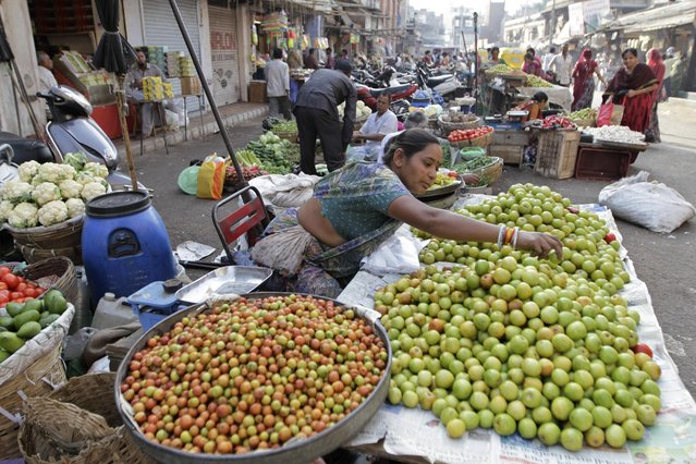 An Indian woman sells berries at a wayside vegetable market in Ahmadabad, India, Monday, February 23, 2015. (Photo by Ajit Solanki/AP Photo)