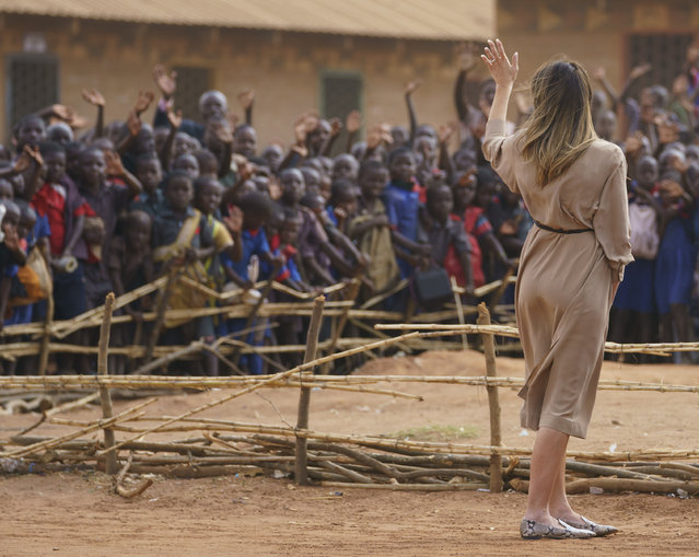First lady Melania Trump waves to children and others as she visits Chipala Primary School, in Lilongwe, Malawi, Thursday, October 4, 2018. Mrs. Trump is visiting Africa on her first big solo international trip, aiming to make child well-being the focus of a five-day, four-country tour. (Photo by Carolyn Kaster/AP Photo)