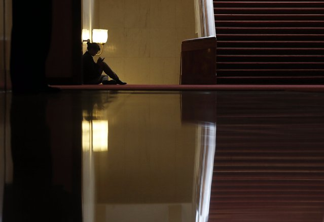 A woman sits inside the Great Hall of the People during the opening session of the Chinese People's Political Consultative Conference (CPPCC) in Beijing, March 3, 2015.  REUTERS/Kim Kyung-Hoon