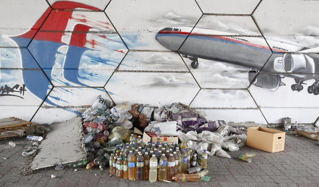 A man sleeps under graffiti depicting the missing Malaysia Airlines flight MH370 on the one year anniversary of its disappearance in Kuala Lumpur, March 8, 2015. Prime Minister Najib Razak said on Sunday Malaysia remains committed to the search for the missing MH370 jetliner a year after it vanished without trace and he is hopeful it will be found. REUTERS/Olivia Harris (MALAYSIA - Tags: TRANSPORT DISASTER SOCIETY POVERTY ANNIVERSARY)