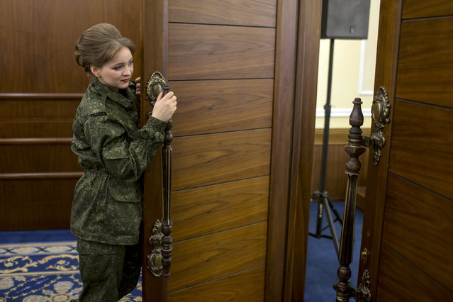 A female soldier of the self-proclaimed Donetsk People's Republic peeks through a door during a beauty pageant to mark International Women's Day in Donetsk, March 7, 2015. (Photo by Marko Djurica/Reuters)
