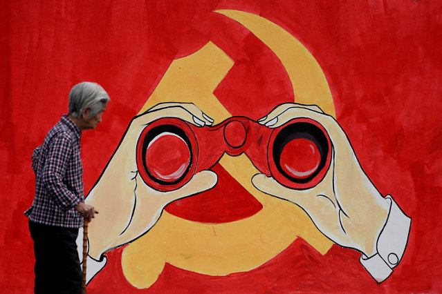A woman stands near a mural showing an emblem of the Communist Party of China along a street in Shanghai, China September 25, 2018. (Photo by Aly Song/Reuters)