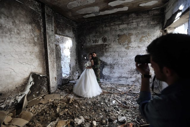 Newly-wed Syrian couple Nada Merhi, 18, and Hassan Youssef, 27, have their wedding pictures taken in a heavily damaged building in the war ravaged city of Homs on February 5, 2016. (Photo by Joseph Eid/AFP Photo)