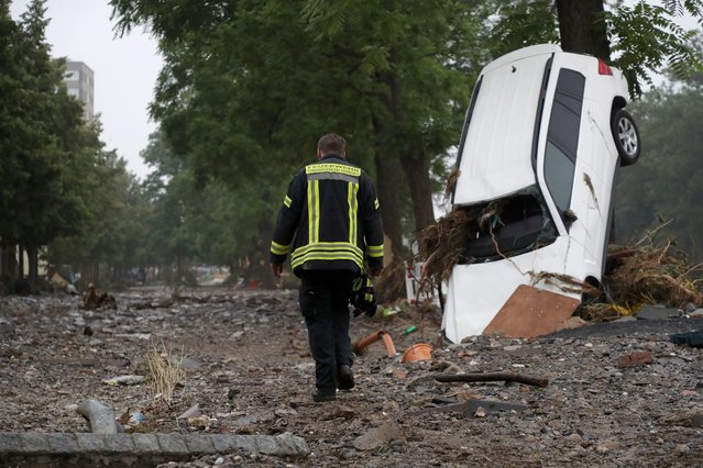 A member of the fire department (Feuerwehr) walks amid the debris near a damaged car after flooding in Bad Neuenahr-Ahrweiler, Germany, 16 July 2021. Large parts of Western Germany were hit by heavy, continuous rain in the night to 15 July resulting in local flash floods that destroyed buildings and swept away cars. (Photo by Friedemann Vogel/EPA/EFE)