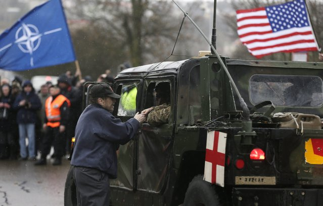 A supporter shakes hands with a US army soldier as their convoy arrives in Prague, Czech Republic, Monday, March 30, 2015. (Photo by Petr David Josek/AP Photo)
