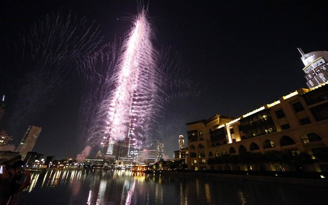 Fireworks illuminate the sky around Dubai's Burj Khalifa, the world's tallest tower, on November 27, 2013, after the Emirati city was chosen to host the World Expo 2020. The Gulf city state beat Russia's Ekaterinberg in the final round of voting to clinch a prestigious event credited with delivering a huge boost to tourism and business for its host city. (Photo by Karim Sahib/AFP Photo)