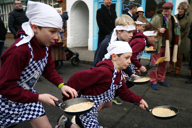Schoolchildren take part in a pancake race on February 9, 2016 in Olney, England. On Shrove Tuesday every year the ladies of Olney, Buckinghamshire compete in a Pancake Race, a tradition which dates back to 1445. Children from Olney schools also take part in their own races. Olney competes every year against the women of Liberal, Kansas, USA in a friendly race dating back to 1950. (Photo by Carl Court/Getty Images)