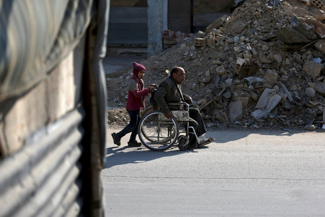 Hadeel, 10, pushes her father Shahrour in his wheelchair through the Douma neighbourhood of Damascus Syria in this February 3, 2016 file photo. (Photo by Bassam Khabieh/Reuters)