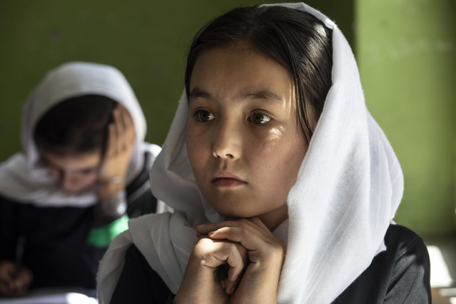 Behishta,11, listens during 4th grade class at the Zarghoona high school on July 25 2021 in Kabul, Afghanistan. The Zarghoona girls high school is the largest in Kabul with 8,500 female students attending classes. The school opened after a nearly two-month break due to the coronavirus (COVID-19) pandemic. Currently there is widespread fear that the Taliban who already control around half the country will reintroduce its notorious system barring girls and women from almost all work, and access to education. The Ministry of Education has announced the opening of schools, but there are  mixed reports in many areas where the Taliban have taken control or where fighting is ongoing. (Photo by Paula Bronstein/Getty Images)