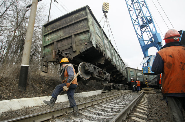 Workers remove a carriage of a train derailed after a blast on a rail track at a railway station in the rebel-controlled town of Yasynuvata, near Donetsk, Ukraine, February 17, 2016. According to the Minister of Transport of the self-proclaimed Donetsk People Republic, it was a blast of a device, which he did not specify. (Photo by Alexander Ermochenko/Reuters)