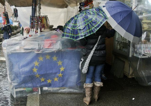 The EU flag wrapped by a plastic sheet, adorns a souvenir stall in downtown Rome, Thursday, February 5, 2015. (Photo by Gregorio Borgia/AP Photo)