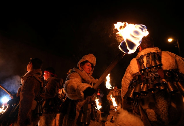"""A woman dressed in a costume made of animal fur, called """"kuker"""", carries a torch during a festival in the town of Batanovtsi, Bulgaria January 13, 2017. (Photo by Stoyan Nenov/Reuters)"""