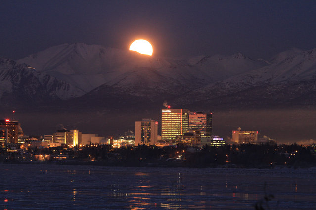 A full moon rises over the Chugach Mountains on Tuesday, February 3, 2015, in Anchorage, Alaska. The temperature in early evening was 9 degrees, continuing February weather featuring clear skies and mild temperatures. (Photo by Dan Joling/AP Photo)