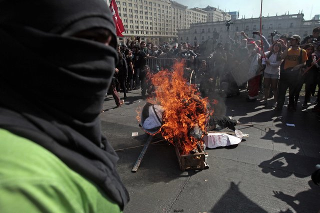 A masked demonstrator stands next to a pile of debris set on fire during a protest near La Moneda Palace in Santiago, Chile, Thursday, April 16, 2015. (Photo by Luis Hidalgo/AP Photo)