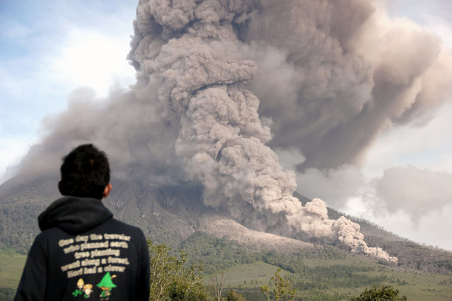 A man watches Mount Sinabung as it spews clouds of gas during an eruption in Tiga Pancur, North Sumatra, Indonesia, Wednesday, January 1, 2014. The 2,600-meter (8,530-foot) volcano has sporadically erupted since September. (Photo by Dedy Zulkifli/AP Photo)