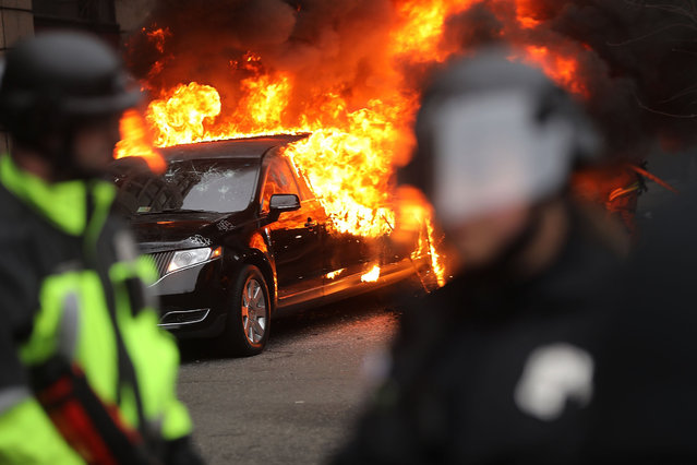 Police and demonstrators clash in downtown Washington after a limo was set on fire following the inauguration of President Donald Trump on January 20, 2017 in Washington, DC. Washington and the entire world have watched the transfer of the United States presidency from Barack Obama to Donald Trump, the 45th president. (Photo by Spencer Platt/Getty Images)