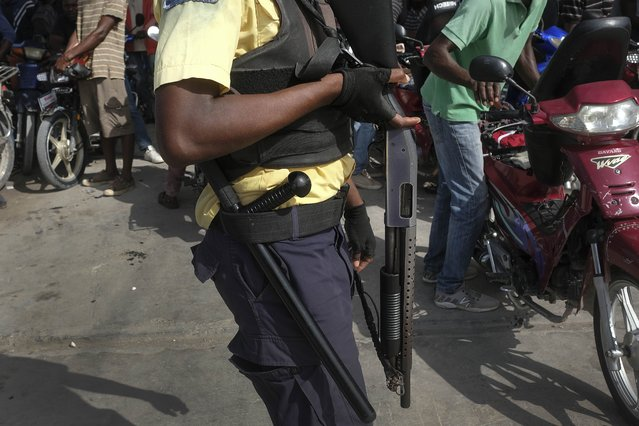 A private security guard keeps order as motorcyclists wait to fill up their gas tanks in Les Cayes, Haiti, Monday, August 23, 2021, a week after a 7.2 magnitude earthquake hit the area. (Photo by Matias Delacroix/AP Photo)