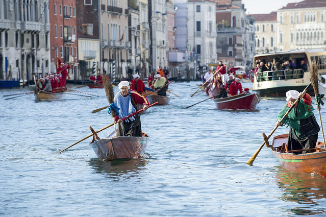"Rowers dressed in costume race along the Grand Canal for the ""Befana"" Regatta on January 6, 2014 in Venice, Italy. In Italian folklore, Befana is an old woman who delivers gifts to children throughout Italy on the feast of the Epiphany on January 6 in a similar way to Saint Nicholas or Santa Claus. (Photo by Marco Secchi/Getty Images)"
