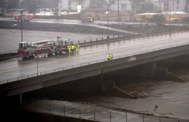 Fire units attempt to locate a possible person in Santa Ana River in Costa Mesa, Calif., during a storm Sunday, January 22, 2017. The heavy downpour on Sunday drenched Orange County in one of the heaviest storms of the year. Fast-moving floodwaters swept through California mountain communities and residents fled homes below hillsides scarred by wildfires as the third in the latest series of storms brought a deluge Sunday and warnings about damaging mudslides. (Photo by Kyusung Gong/The Orange County Register via AP Photo)