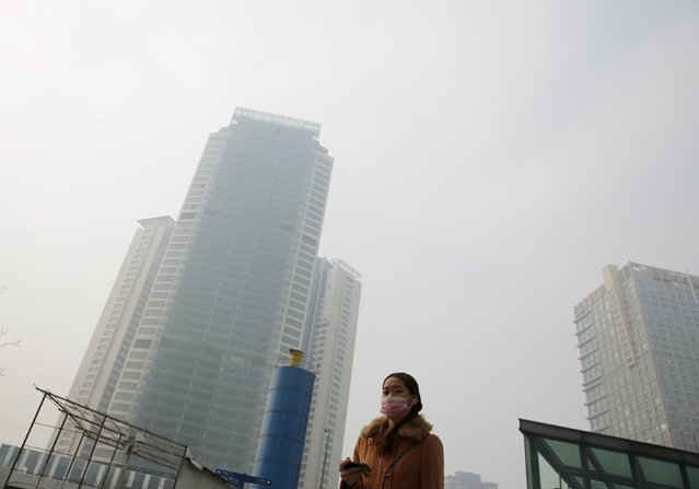 A woman wearing a mask makes her way on a hazy day at a business district in Beijing April 10,  2015. (Photo by Kim Kyung-Hoon/Reuters)