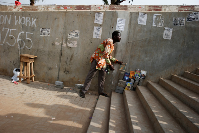 A man arranges books for sale on a pedestrian bridge where posters advertising jobs are pasted, in Ojodu district in Nigeria's commercial capital Lagos December 22, 2016. (Photo by Akintunde Akinleye/Reuters)
