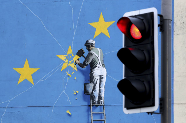 A view of the Banksy Brexit mural of a man chipping away at the EU flag in Dover, England, Tuesday, December 11, 2018. Top European Union officials on Tuesday ruled out any renegotiation of the divorce agreement with Britain, as Prime Minister Theresa May fought to save her Brexit deal by lobbying leaders in Europe's capitals. (Photo by Gareth Fuller/PA Wire via AP Photo)