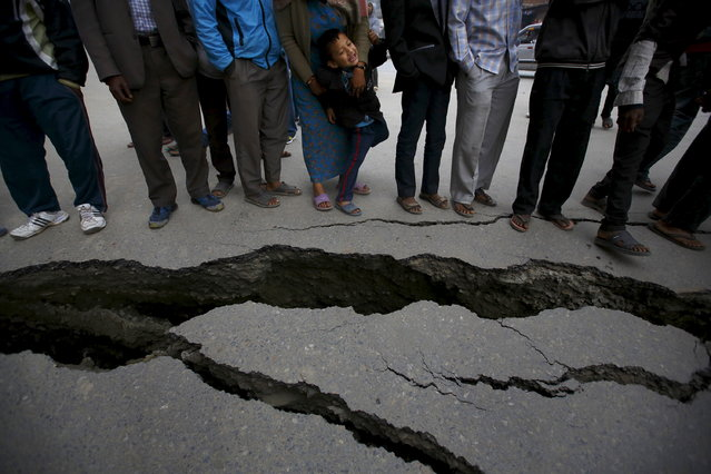 People gather near the cracks on the road caused by an earthquake in Bhaktapur, Nepal April 26, 2015. (Photo by Navesh Chitrakar/Reuters)
