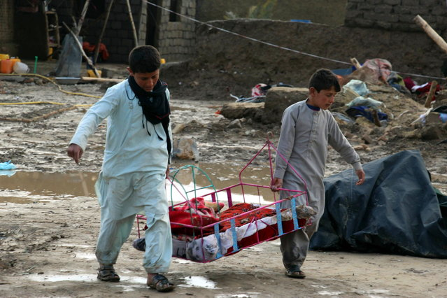 People salvage their belongings after flash floods in Kandahar, Afghanistan, 02 March 2019. At least 20 people including children were killed after flash floods and torrential rains in southern Afghanistan while thousands of houses were damaged. (Photo by Muhammad Sadiq/EPA/EFE)