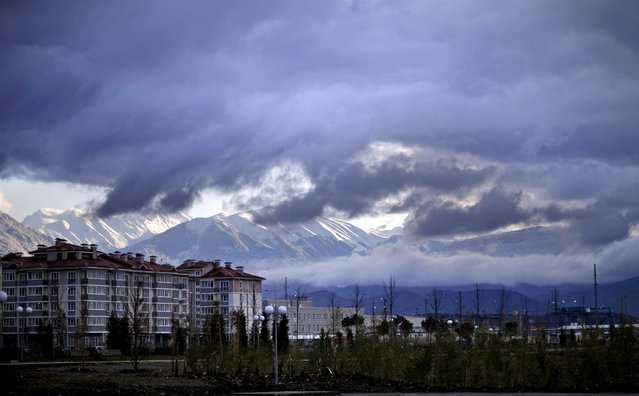The Caucasus Mountains, site of the 2014 Winter Olympic outdoor snow sport and sliding track events, rise above a recently built housing complex, at left, near the Olympic Park by the Black Sea in the Coastal Cluster, Saturday, February 1, 2014, in Sochi, Russia. (Photo by David Goldman/AP Photo)