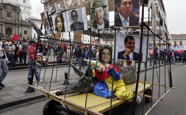 A parade float that represents the lack of freedom by encaging a rat and a clown, surrounded by images of Ecuador's President Rafael Correa and the community leaders who support him, arrives at the San Francisco Plaza at the end of an anti-government march, marking May Day, in Quito, Ecuador, Friday, May 1, 2015. (Photo by Dolores Ochoa/AP Photo)
