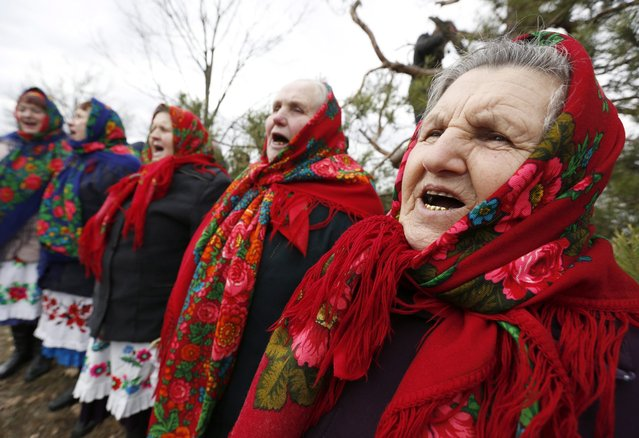 Belarusians dressed in traditional clothes sing traditional songs as they celebrate the Chyrachka rite in the village of Tonezh, some 280 km from Minsk, Belarus, 13 March 2016. The Chyrchka rite is held on the last day of Maslenitsa, or Shrovetide. Chyrachka is a local name of a small duck, a teal. Figures of a teal are baked on this day in the form of a fancy cake and participants of the rite hand them out to all whom they meet on their way to a hill, inviting them to join. It is believed that teals bring spring on their wings. (Photo by Tatyana Zenkovich/EPA)