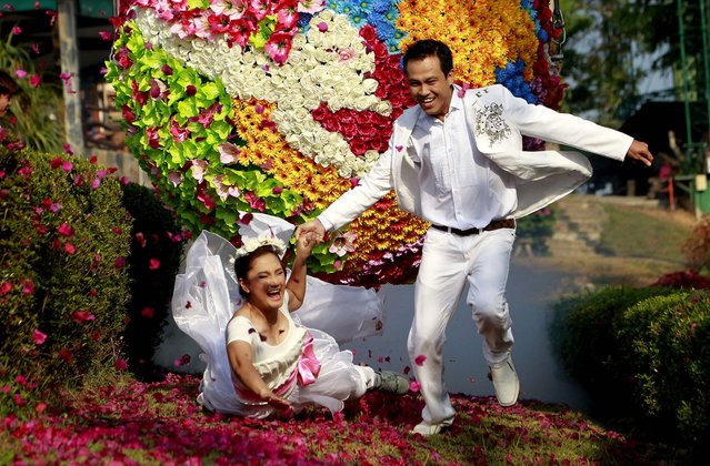 Groom Wichan Vina, 32, holds the hand of his bride Wilailuk Roongros, 31, who fell on the ground as they both run from a giant ball decorated with flowers, called Run Way of Love, in Prachinburi province, Thailand, on February 13, 2014. They celebrated their wedding on the eve of Valentine's Day. (Photo by Wason Wanichakorn/Associated Press)