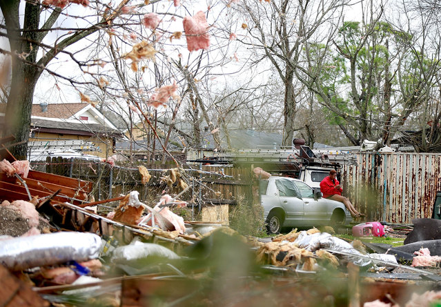 A woman sits on a car surronded by debris along Chef Menture Ave after a tornado touched down in the eastern part of the city on February 7, 2017 in New Orleans, Louisiana. (Photo by Sean Gardner/Getty Images)
