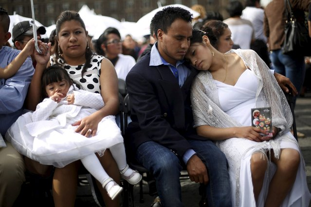 A bridal couple waits before a mass wedding ceremony in which 2,016 couples participated, at Zocalo square in Mexico City, Mexico, March 19, 2016. (Photo by Edgard Garrido/Reuters)