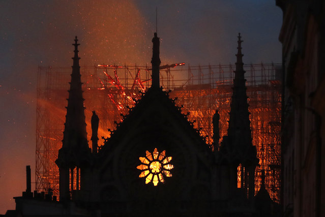 Flames and smoke rise from Notre Dame cathedral as it burns in Paris, Monday, April 15, 2019. Massive plumes of yellow brown smoke is filling the air above Notre Dame Cathedral and ash is falling on tourists and others around the island that marks the center of Paris. (Photo by Thibault Camus/AP Photo)