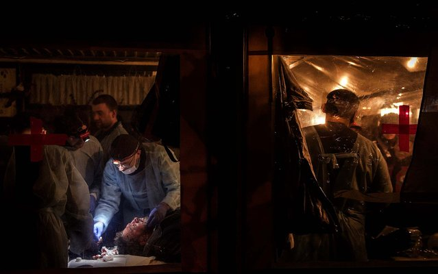 Medical volunteers treat a wounded man in a makeshift medical tent at the protest camp in Independence Square in Kiev, on February 19, 2014. (Photo by Sergey Ponomarev/The New York Times)
