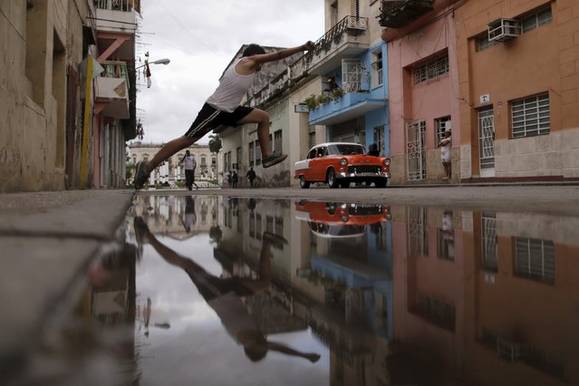 A boy jumps over a puddle of water on the outskirts of Havana, Cuba March 21, 2016. (Photo by Ueslei Marcelino/Reuters)