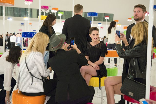 Women take pictures of U.S. actress Kristen Stewart after the Chanel Cruise Collection 2015/16 fashion show at the Dongdaemun Design Plaza in Seoul, May 4, 2015. (Photo by Thomas Peter/Reuters)