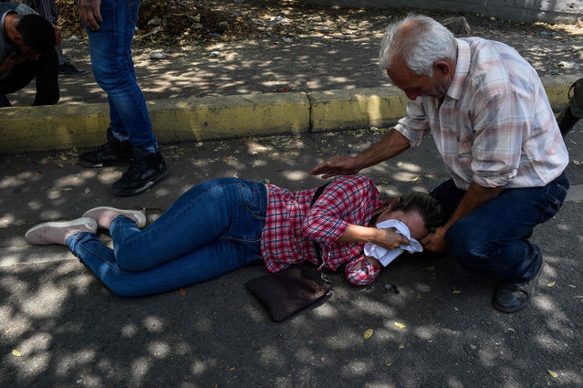 An opposition demonstrator affected by tear gas is assisted during clashes with soldiers loyal to Venezuelan President Nicolas Maduro after troops joined opposition leader Juan Guaido in his campaign to oust Maduro's government, in the surroundings of La Carlota military base in Caracas on April 30, 2019. (Photo by Federico Parra/AFP Photo)